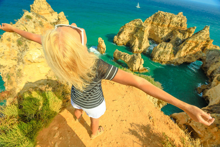 Tourism in Algarve. Freedom lifestyle tourist looking at amazing views of Ponta da Piedade promontory. Caucasian carefree woman enjoying iconic cliffs of Lagos. Summer holidays in Portugal, Europe. Lagos Portugal Algarve Portugal Algarve Coastline Algarve Beach Algarve Cliffs And Beach Beach Sea Town Seascape Boat Portrait Pier Aerial View Cliff Jetty Boats Woman Females Girl Selfie Model Ponta Da Piedade Ponta Da Piedade Lagos Lighthouse Bay Water Blond Hair Hair One Person Nature Real People Leisure Activity Land Lifestyles Women Day Casual Clothing Rock High Angle View Rock - Object Solid Rear View Hairstyle Outdoors Human Arm