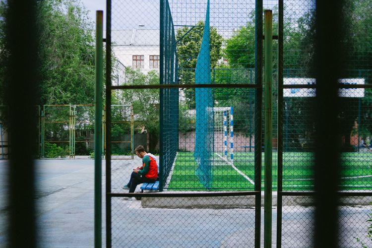 Man sitting by sitting by baseball court