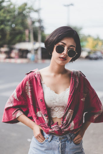 Portrait of sensuous woman wearing sunglasses while standing on road