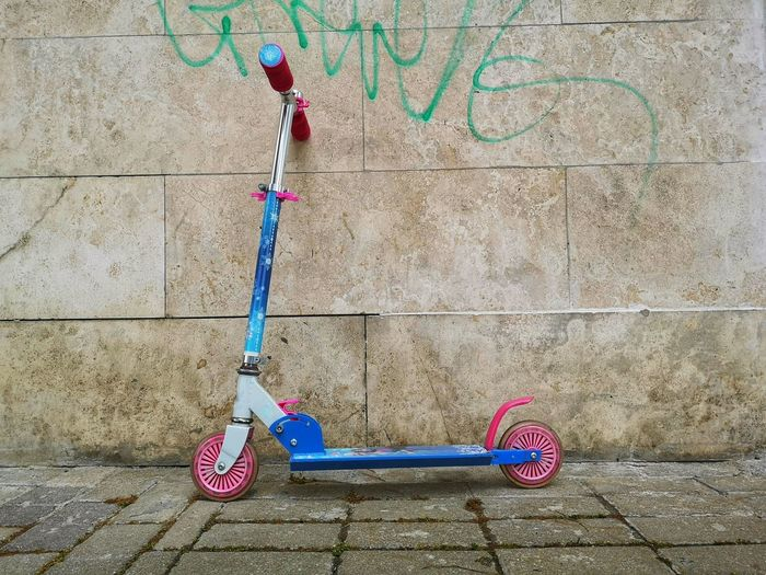 scooter for children leaning against the wall Scooter Day Push Scooter No People Transportation Outdoors Pink Color Mode Of Transportation Wall Street Multi Colored Single Object Children