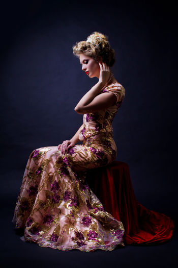 Side view of woman in evening gown sitting against black background