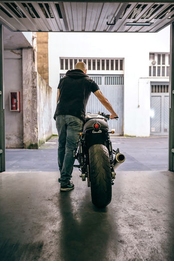 Rear view of man walking with motorcycle from garage