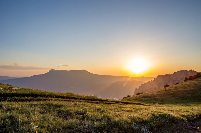 Beauty In Nature Bright Environment Grass Idyllic Land Landscape Lens Flare Mountain Mountain Range Nature No People Non-urban Scene Outdoors Plant Scenics - Nature Sky Sun Sunbeam Sunlight Sunset Tranquil Scene Tranquility