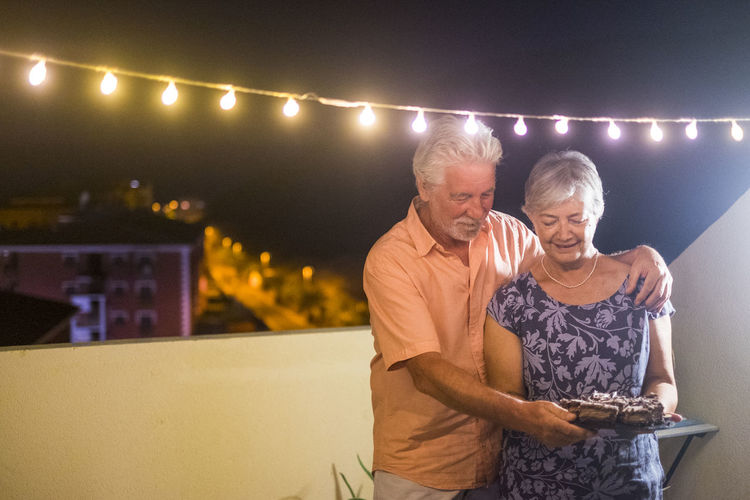Happy senior adult couple with a chocolate cake after dinner at home outdoor in the terrace with party bulb light - birthday concept or new year celebration for matures people - Illuminated Two People Togetherness Men Adult Front View Emotion Lifestyles Happiness Night Smiling Real People Women Males  Lighting Equipment Bonding Leisure Activity Mature Adult People Casual Clothing Couple - Relationship Mature Men Positive Emotion Arm Around Elderly People Senior Adult Grandparents Dusk Foodeating Terraced Field Lights Chocolate Cake Sweet Food Dress