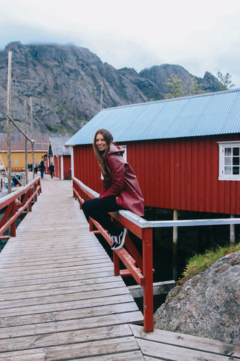Mountain Architecture Built Structure Mountain Range Building Exterior Day Nature Outdoors Norway Houses Fisherhouse Ocean Fjord One Person Real People Women Wood - Material Young Adult Leisure Activity Rain Jacket Outdoor Wear Woman Girl
