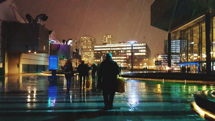 Rain Wet Reflection Full Length Illuminated Rainy Season Water Business Night Rear View Adults Only People City Architecture Real People RainDrop Adult Outdoors Snow ❄ Snow Snowy Utrecht , Netherlands Jaarbeurs Utrecht Jaarbeursplein Adapted To The City Mobility In Mega Cities