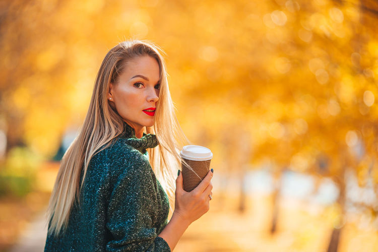 Portrait of woman holding coffee during autumn