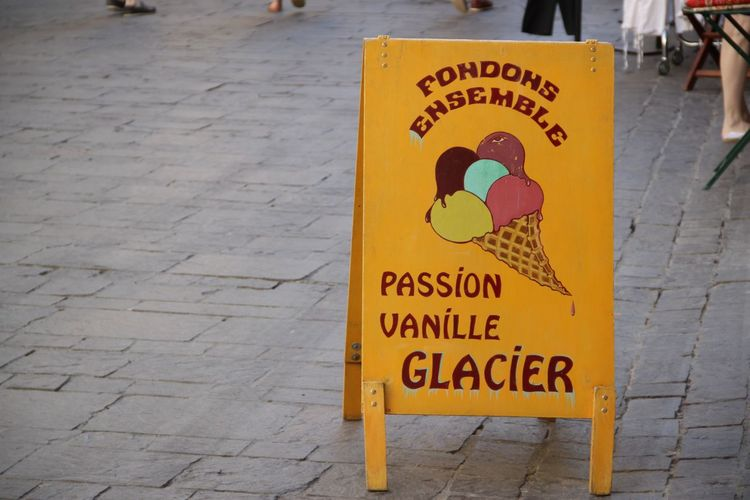 Sign Board On Footpath Outside Ice Cream Parlor
