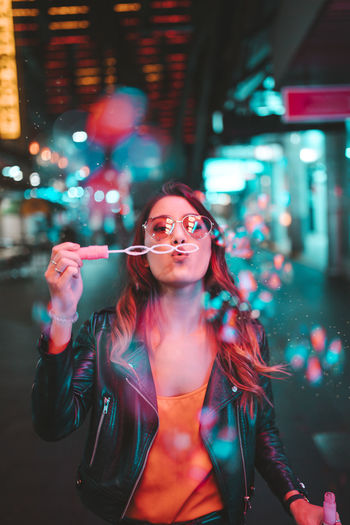 Portrait of young woman wearing sunglasses standing at night