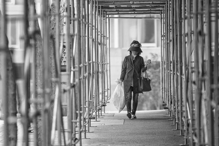 Woman carrying plastic bag on footbridge