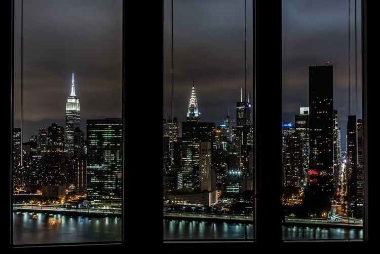 Empire State Building Amidst Illuminated Towers Seen Through Window