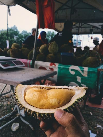 Cropped hand holding durian