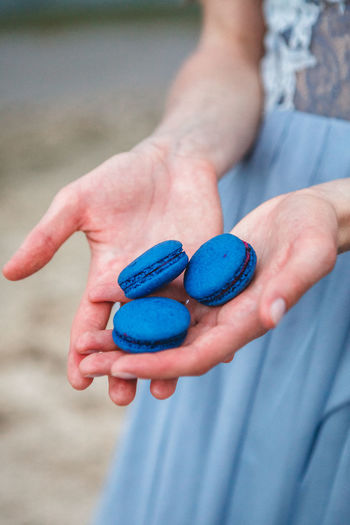 Midsection of woman holding blue macaroons