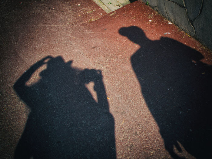 Shadow of man photographing on street