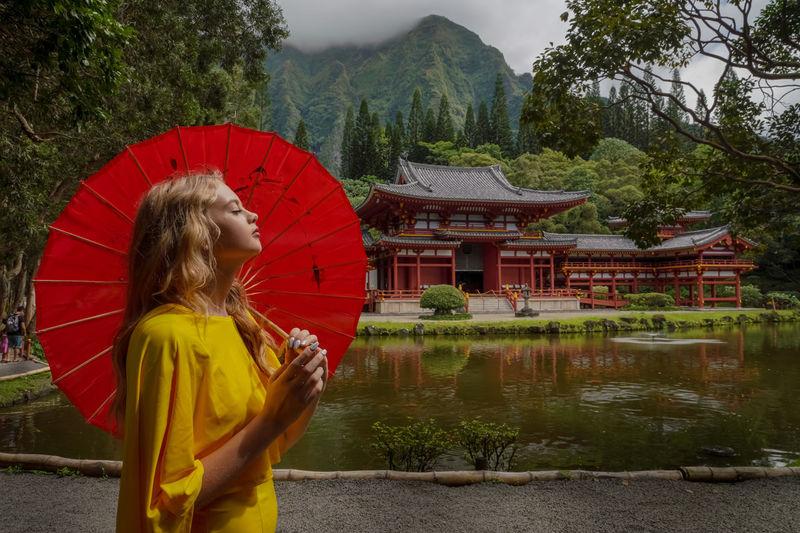 Woman standing by lake against temple