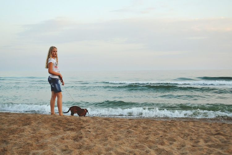 Girl with dog at beach against sky