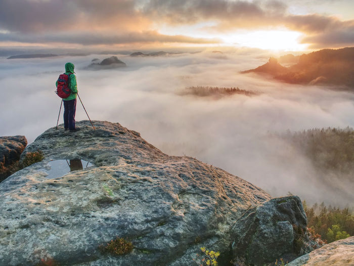 Emale hiker enjoying the view on the soutern rim of saxony switzerland within extreme autumn weather