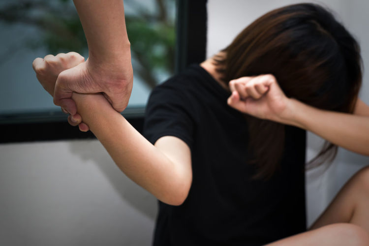 Cropped hand holding wrist of woman at home
