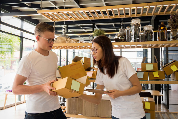 Man giving boxes to woman