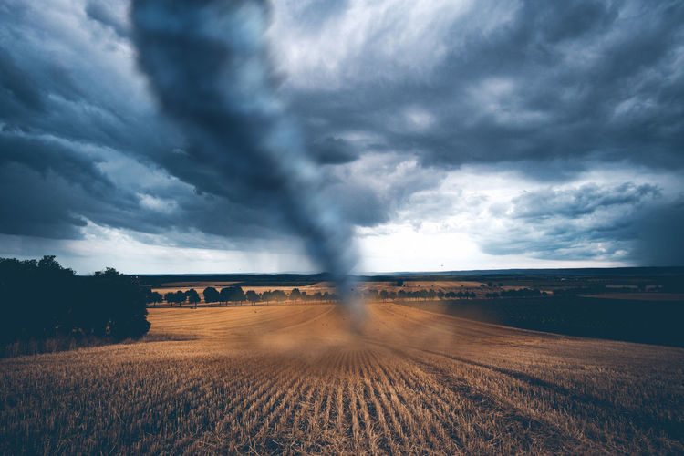 Tornado on land against storm clouds