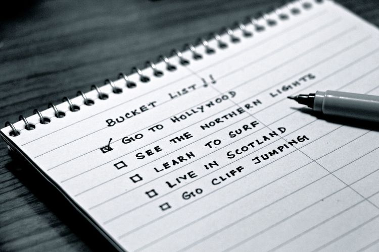 Close-up of bucket list written on note pad