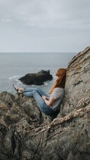 Woman sitting on rocky shore against sky