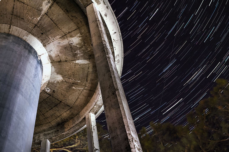 Low angle view of water tower against star trail sky