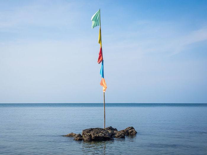 Multi colored flag pole in the sea on Koh Jum, Thailand Thailand Beauty In Nature Blue Day Flag Horizon Horizon Over Water Idyllic Koh Jum Multi Colored Nature No People Outdoors Rock Rock - Object Scenics - Nature Sea Sky Tranquil Scene Tranquility Water Waterfront