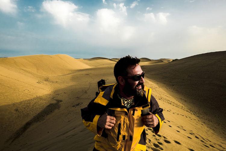 Man standing at desert against sky