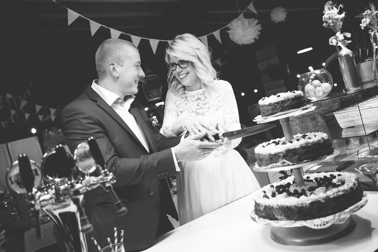 Tilt shot of newlywed young couple cutting cake during wedding reception