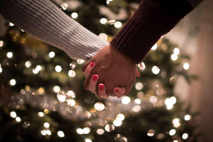 Cropped image of couple holding hands against christmas tree