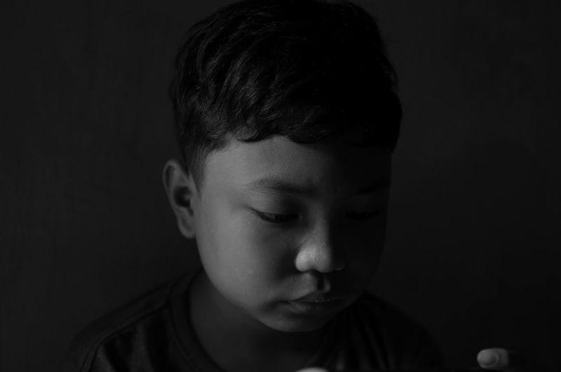 Close-up of sad boy in darkroom