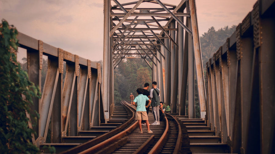 People standing on railway bridge against sky