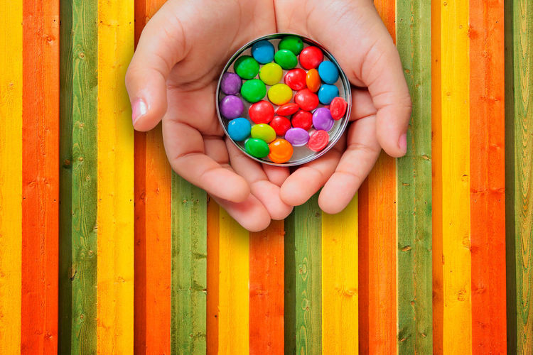 Body Part Candy Child Childhood Day Directly Above Finger Hand Holding Human Body Part Human Hand Large Group Of Objects Leisure Activity Lifestyles Multi Colored People Real People Sweet Sweet Food Wood - Material