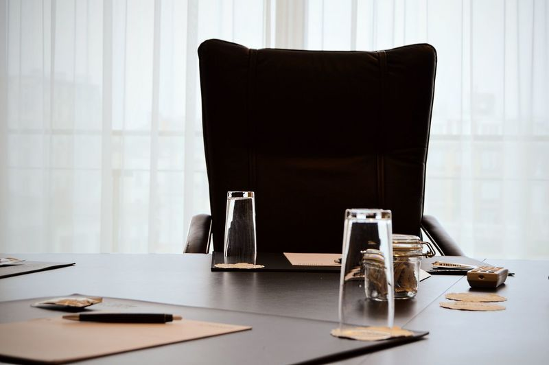 Close-up of office desk by empty chair