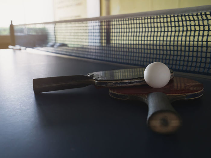 Old table tennis rackets and balls placed on table tennis