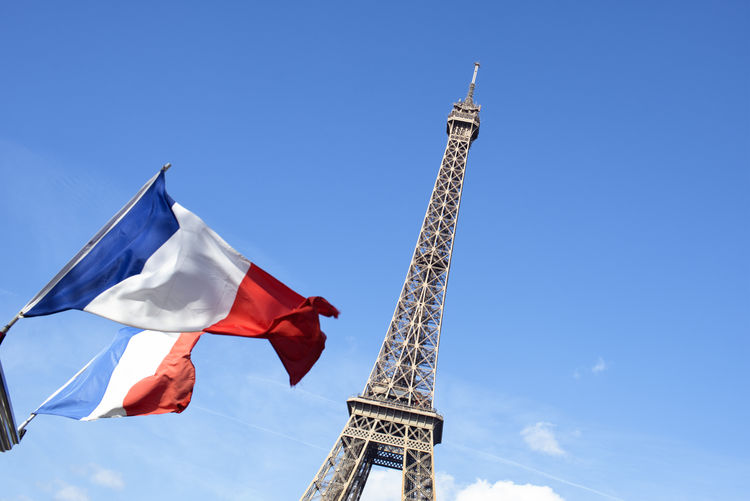 Low Angle View Of French Flags And Eiffel Tower Against Sky