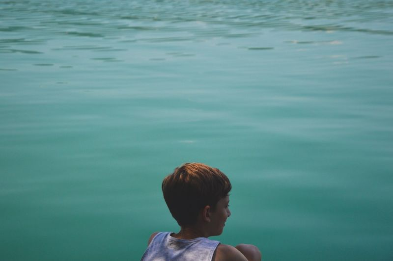 Rear view of boy against turquoise lake