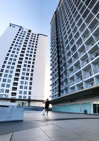 Man walking by modern buildings in city against sky
