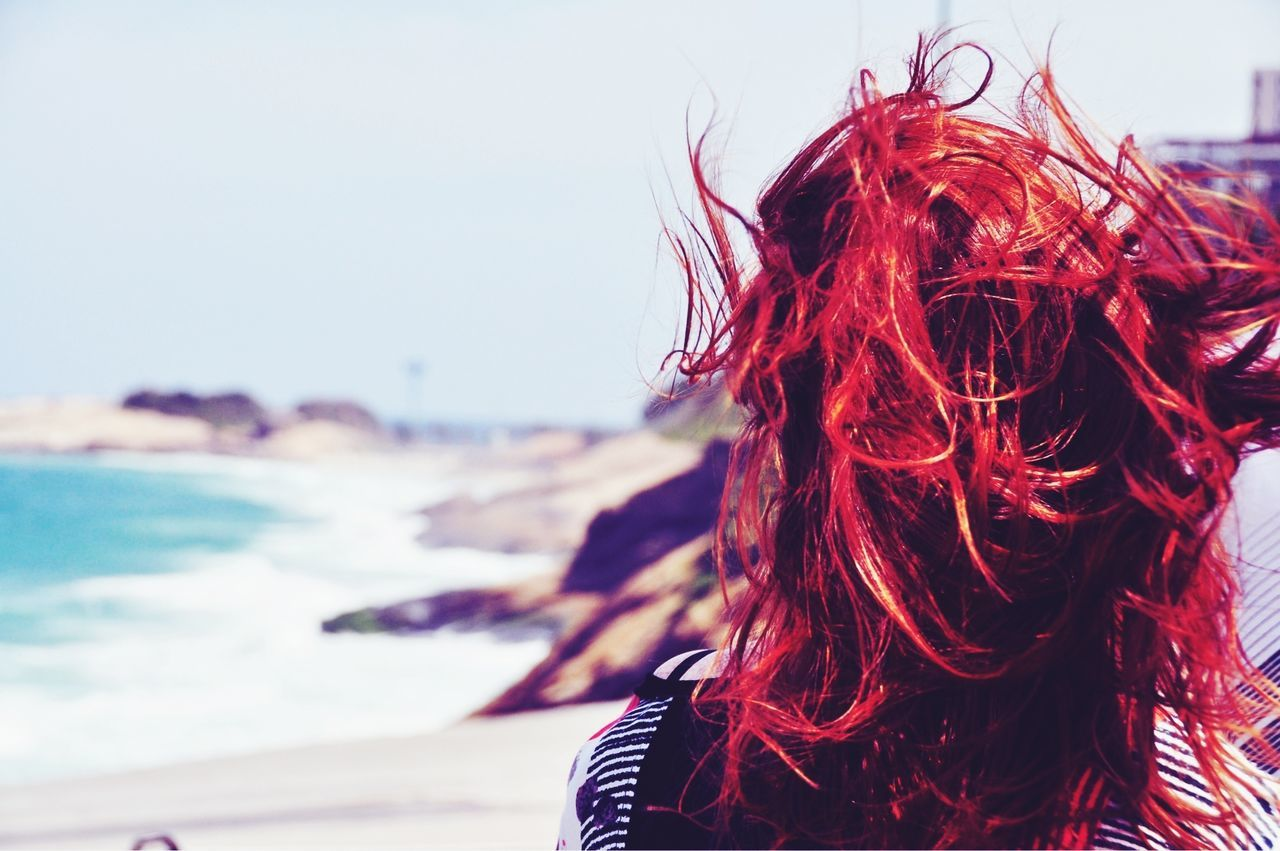 A rear view of a red haired woman walking on a beach