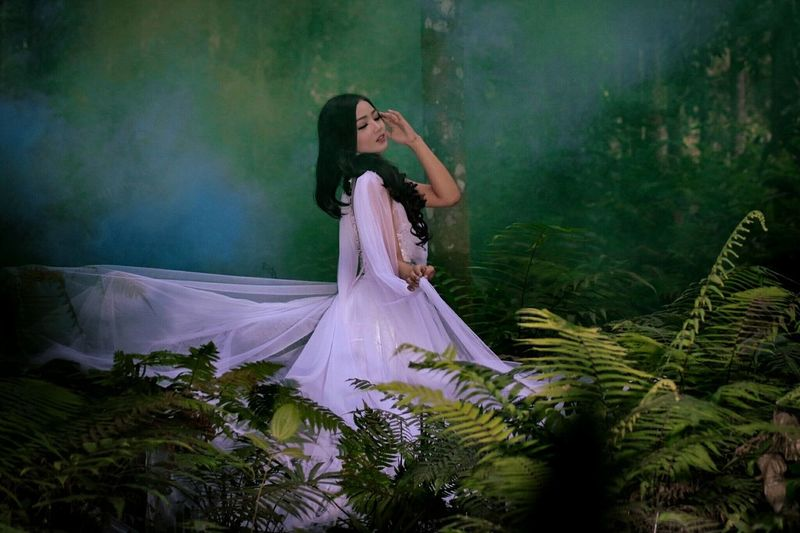 Side View Of Woman Wearing Purple Evening Gown Standing By Plants In Forest