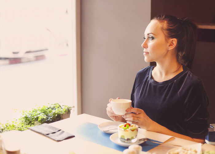 Woman looking away while sitting on table at home