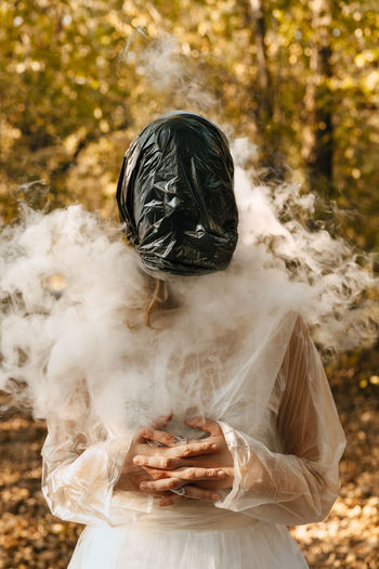 Woman wearing plastic bag in forest