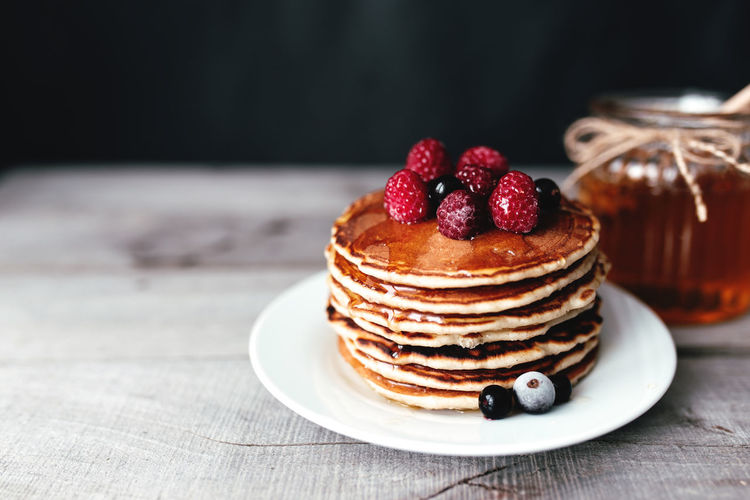 Juicy pancakes with berries and honey on a white plate, spoon, jar, wooden table. high quality photo