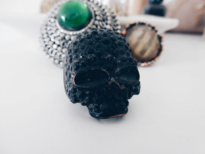 Skull Shaped Ring And Personal Accessory On Table