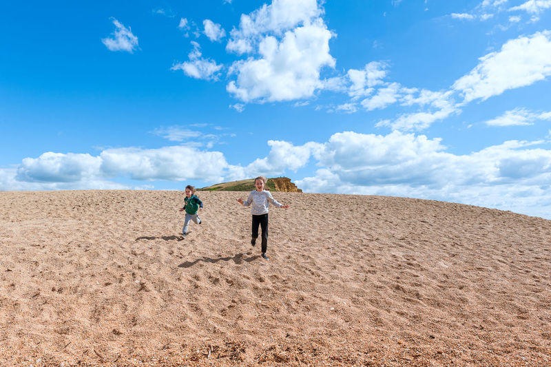 Low angle view of kids walking on sand dune against sky