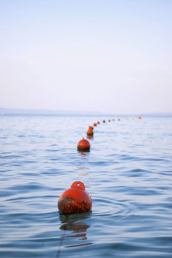 Floating buoys. Array Border Line Buoy Buoys Filthy Floatage Floating On Water Immensity Impurities Impurity Infinitude Limitless LINE Rippled Row Sequence String To The Infinite Unlimited Waterfront Twilight View