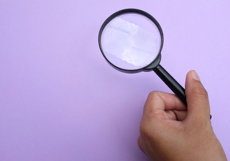 Close-up of hand holding magnifying glass against purple background