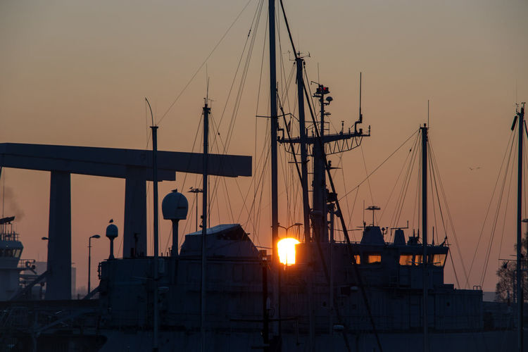 Silhouette sailboats moored on harbor against sky during sunset
