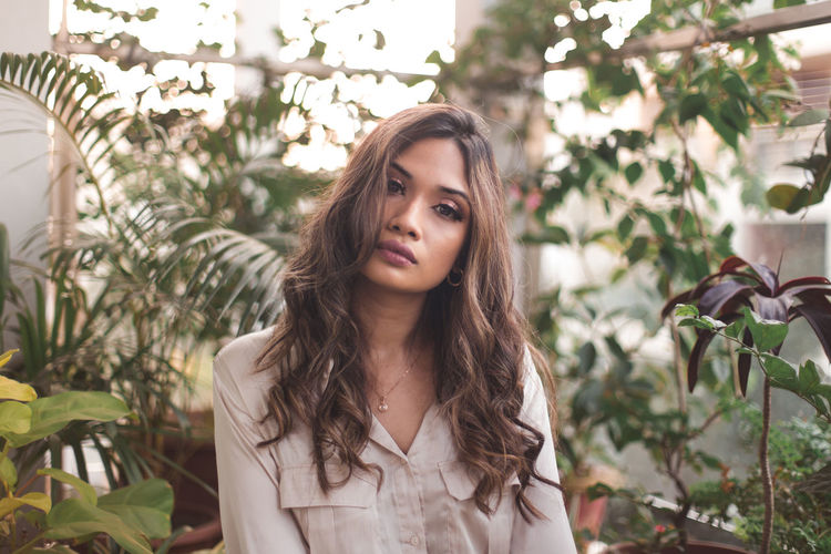 Portrait of young woman sitting against plants